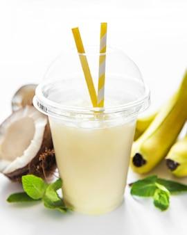 Cocktail fresco alcolico di pina colada servito freddo con cocco e banana su sfondo bianco