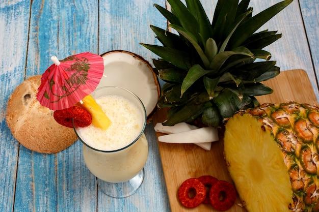 Piña colada con frutta fresca sul tagliere di legno sul fondo del tavolo del bordo bianco