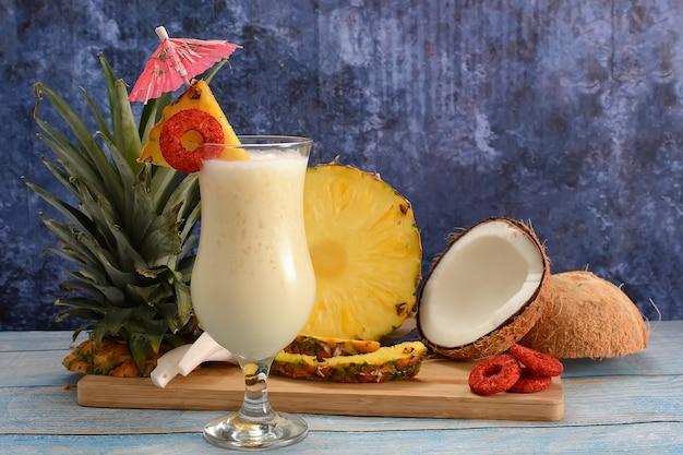 Piña colada con frutta fresca su tagliere di legno su tavola bianca e sfondo blu