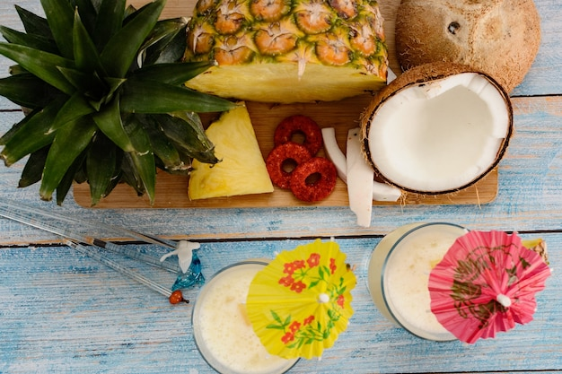 Piñas coladas con frutta fresca su tagliere di legno su tavola bianca e sfondo blu
