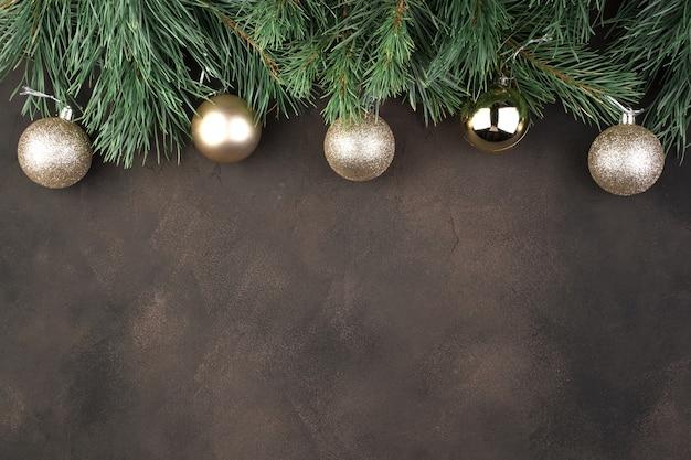 Rami di pino e palle di natale su uno sfondo marrone
