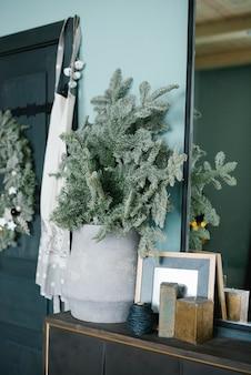Rami di pino in un vaso di ceramica grigia nell'arredamento del soggiorno o della sala da pranzo, decorato per il natale