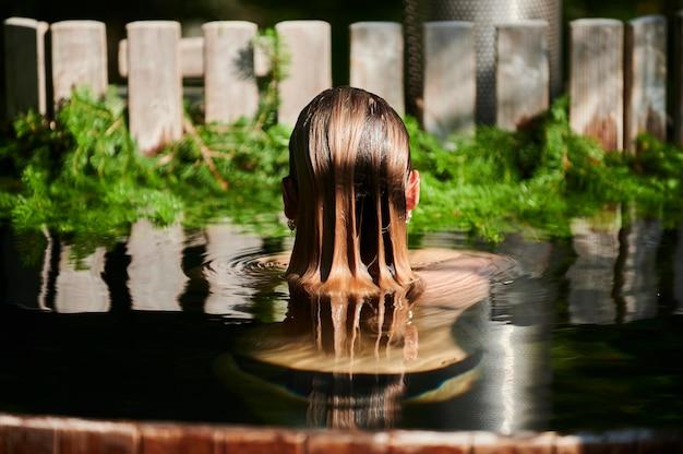 Rami di pino vicino a una conifera calda in un'acqua della spa del tubo caldo