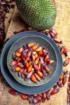 Pigna e pinoli (tipico seme di araucaria usato come condimento nella cucina brasiliana). pinoli, tipico cibo invernale su superficie in legno.