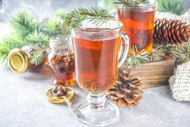 Tè del cono di pino, bevanda calda aromatica del tè invernale biologico con ramo di pino e marmellata di pigna, concetto di bevanda invernale dolce e salutare