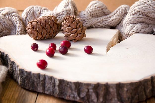 Pigne e mirtilli rossi su un supporto di legno.