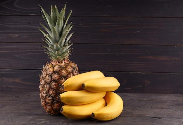 Ananas e banane su una superficie scura