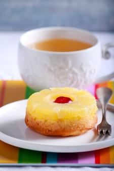 Mini torta di ananas e ciliegia e tazza di tè