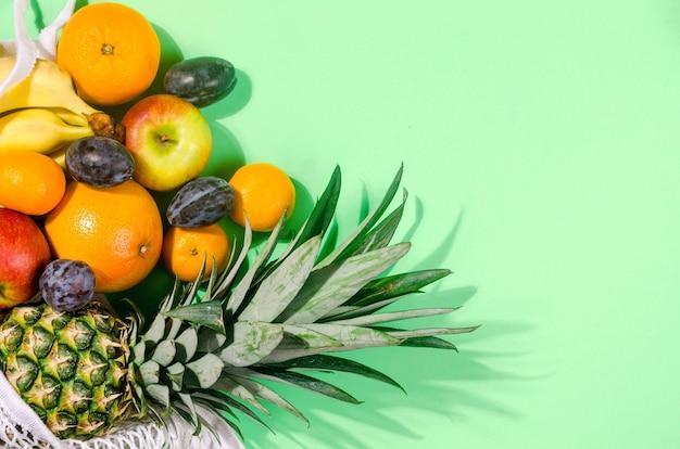 Ananas. cocco, arancia, banane in borsa della spesa su sfondo verde chiaro