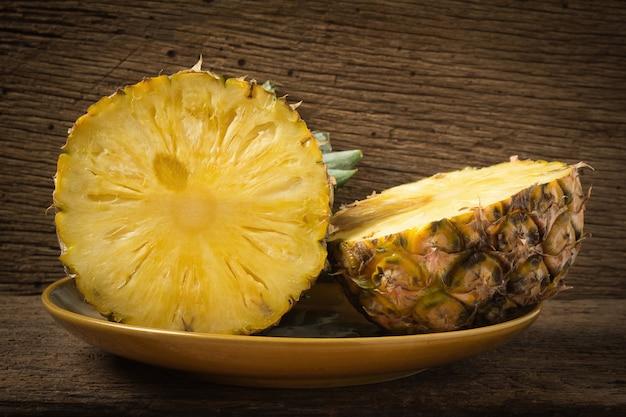 Ananas sul piatto a metà su legno vecchio