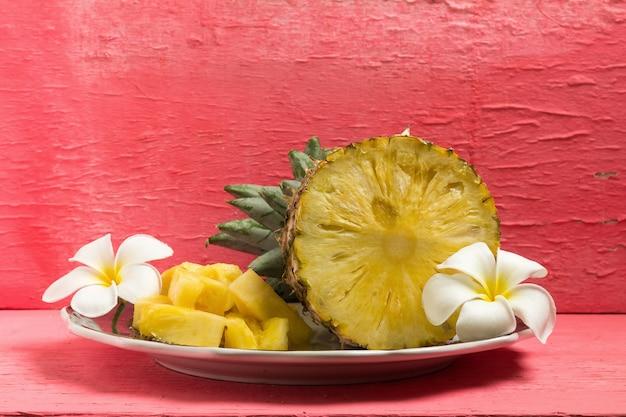 Ananas sul piatto a metà con il fiore sul legno rosa