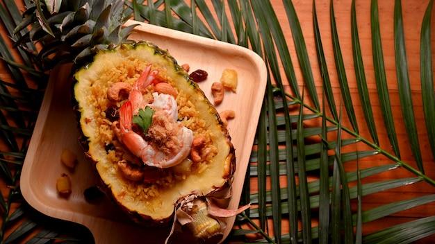 Riso fritto all'ananas (kao pad sapparod) in una ciotola di ananas tagliata e foglie decorate sul tavolo