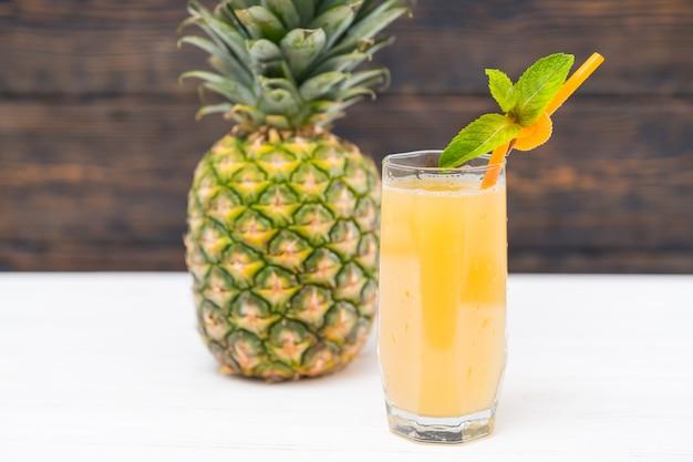 Frutta ananas con un bicchiere di succo di frutta fresco