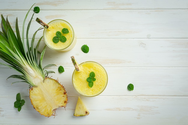 Succo di ananas su superficie di legno bianca