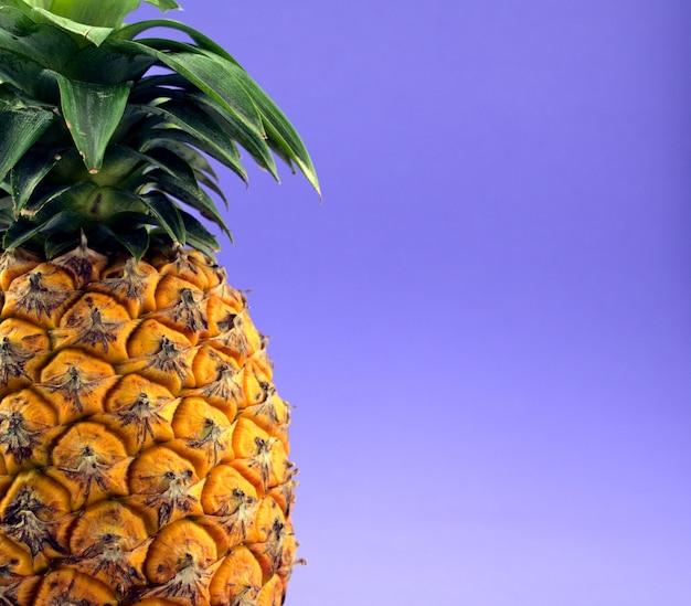 Frutta tropicale succosa di ananas contro il fondo astratto di struttura blu