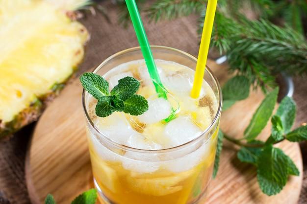 Limonata di ananas con menta su uno sfondo di legno