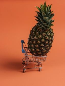 Ananas in un mini carrello della spesa su sfondo color corallo