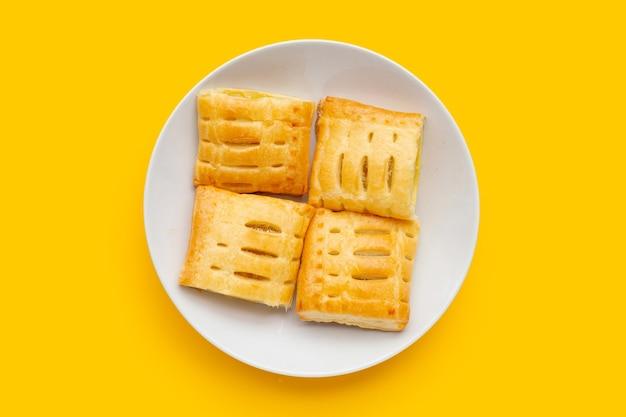 Torta di ananas in piatto bianco su sfondo giallo.