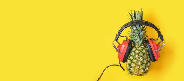 Ananas in cuffie retrò rosse su sfondo giallo con spazio di copia