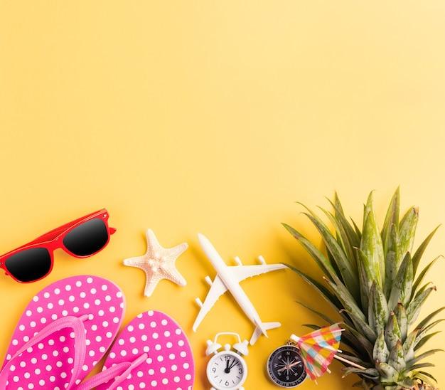 Ananas, occhiali da sole, modello di aereo, stelle marine e sveglia su giallo, piatto