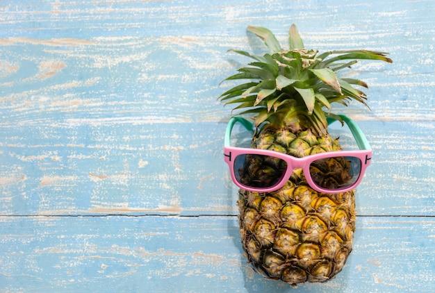 Frutta tropicale dell'ananas con gli occhiali da sole rosa su superficie di legno stagionata blu