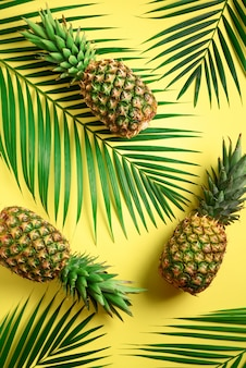 Ananas e foglie di palma tropicali su sfondo giallo. la disposizione piatta creativa con lo spazio della copia.
