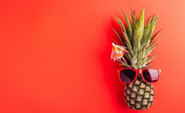 L'ananas indossa occhiali da sole rossi su rosso