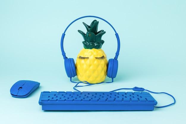 Ananas che indossa le cuffie con tastiera e mouse