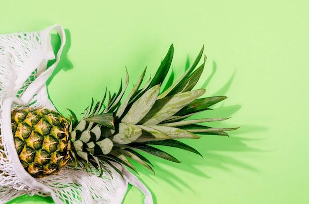 Ananas in borsa della spesa bianca su sfondo verde chiaro