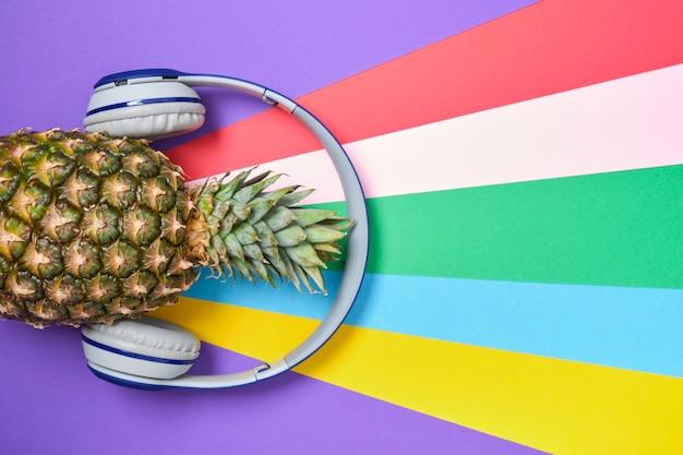 Ananas in cuffie wireless su uno sfondo luminoso colorato vista dall'alto dello spazio copia copy