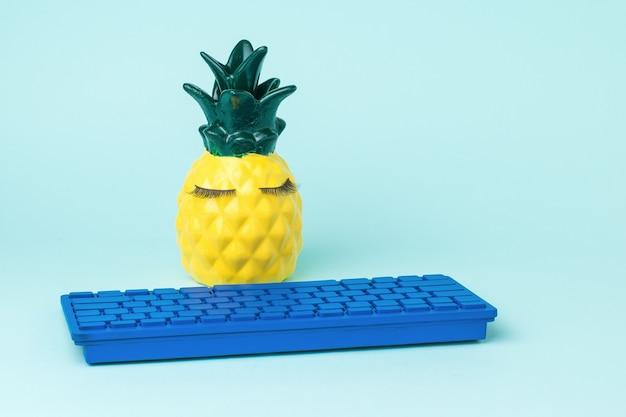 Ananas con una tastiera blu brillante su sfondo chiaro. il concetto di digitalizzazione globale.