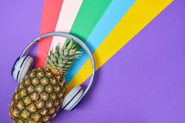 Ananas con le cuffie su uno sfondo colorato con copia spazio, vista dall'alto