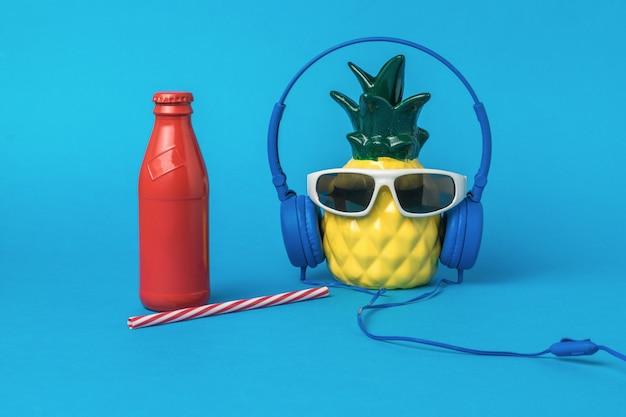Ananas con cuffie e occhiali e una bottiglia di bevanda rinfrescante su sfondo blu. concetto di estate.