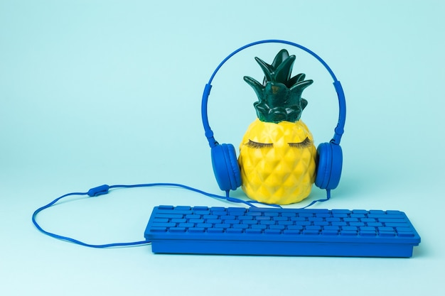 Ananas con tastiera e cuffie su una superficie blu. il concetto di digitalizzazione globale.