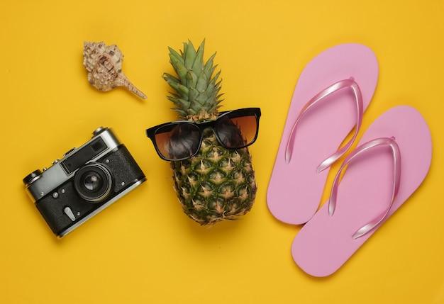 Ananas con occhiali da sole, infradito, fotocamera su sfondo giallo. vista dall'alto
