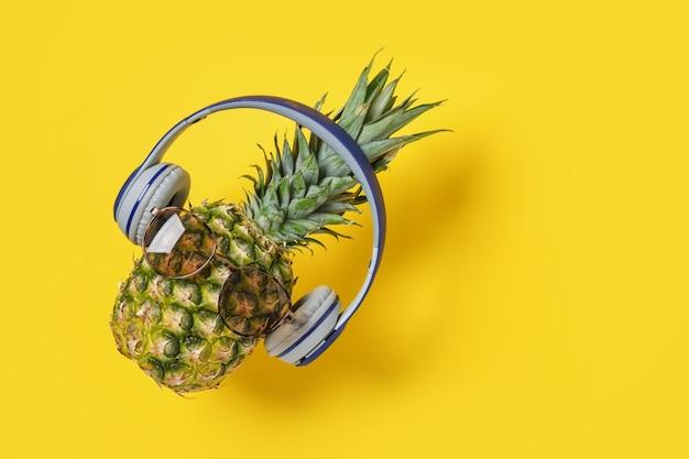Ananas con occhiali da sole e cuffie su sfondo giallo