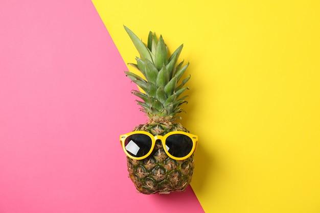 Ananas con occhiali da sole su due toni, spazio per il testo