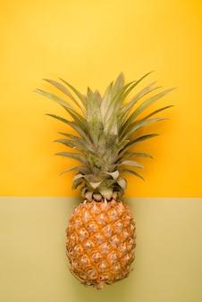 Ananas su superfici gialle e verdi