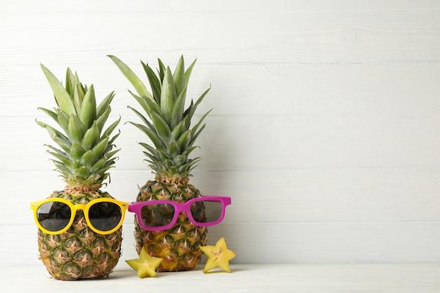 Ananas con occhiali da sole su legno bianco, spazio per il testo