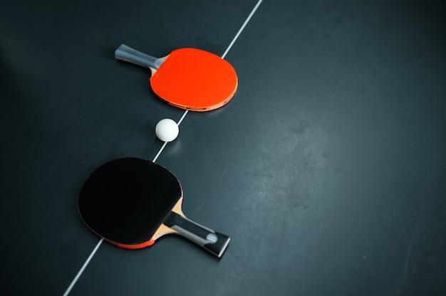 Pallina da ping pong e due racchette sulla linea bianca, vista dall'alto, nessuno, concetto di tennis da tavolo