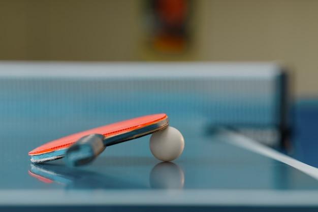 Racchetta da ping pong e palla sul tavolo da gioco con rete, nessuno, primo piano. club di ping-pong, concetto di tennis, simbolo di ping-pong