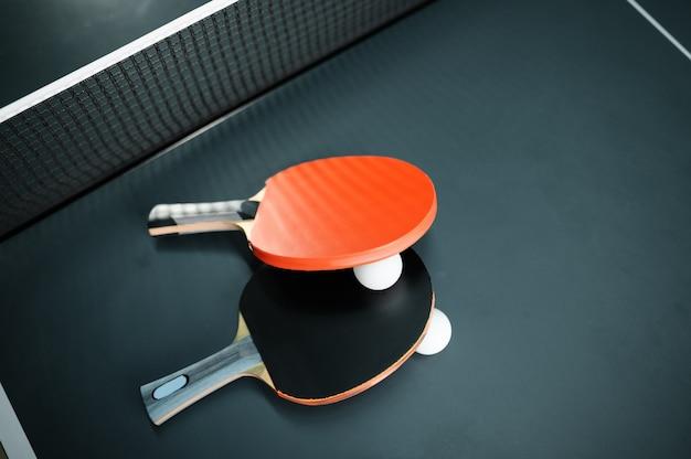 Racchette da ping pong e palla al primo piano netto, nessuno, concetto di ping-pong