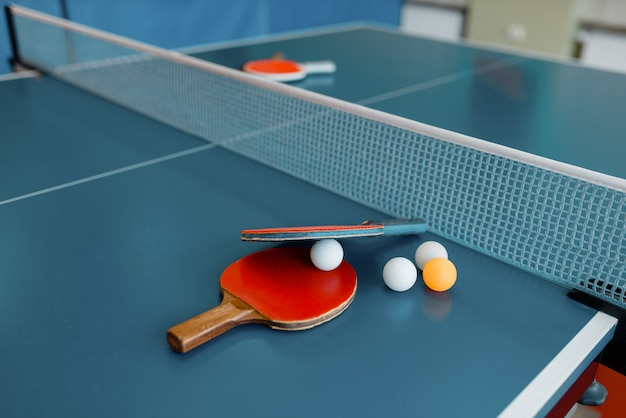 Racchette da ping pong e palline sul tavolo da gioco con rete