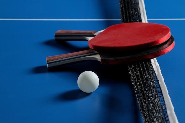 Racchette da ping pong con una palla sul tavolo