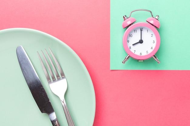 Rosa sveglia, forchetta, coltello e piatto vuoto su sfondo di carta colorata. concetto di digiuno intermittente- immagine