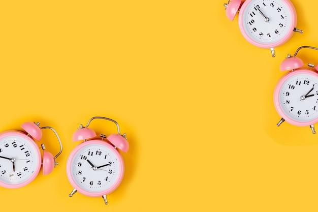 Sveglia rosa su sfondo giallo.