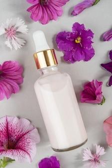 Collagene rosa antietà, siero viso o altro prodotto cosmetico in bottiglia di vetro tra i fiori viola su sfondo grigio.
