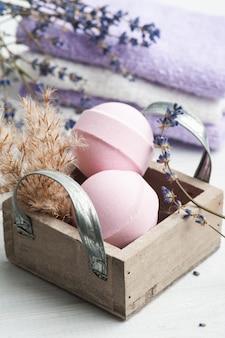 Bombe da bagno aromatiche rosa nella composizione spa con fiori di lavanda secca e asciugamano
