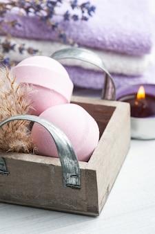 Bombe da bagno aromatiche rosa nella composizione spa con fiori di lavanda secca e asciugamani. disposizione di aromaterapia, natura morta zen con candela accesa