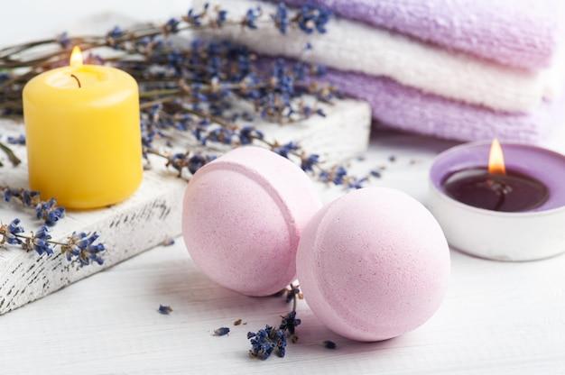 Bombe da bagno aromatiche rosa nella composizione spa con fiori di lavanda secca e asciugamani. disposizione di aromaterapia, natura morta zen con candele accese